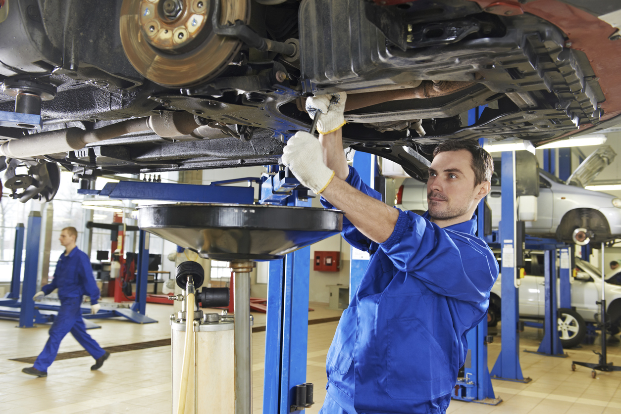 An auto mechanic repairing the suspension on a car